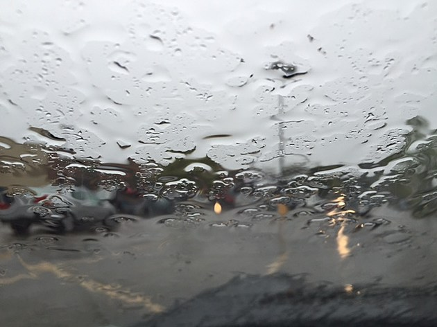 A windshield wet with rain from inside the car.