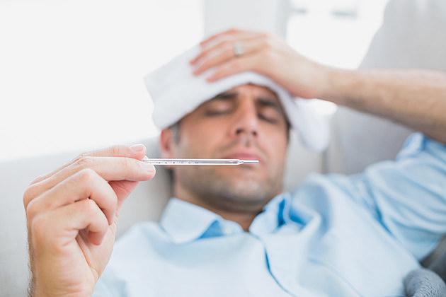 Sick man lying on sofa checking his temperature